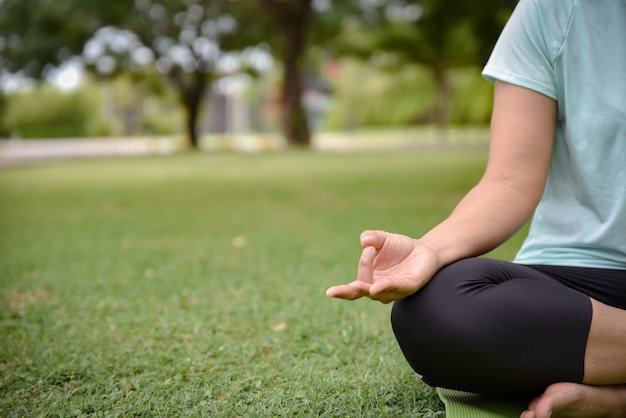 Close up of woman hands do yoga outdoors in the park. Premium Photo