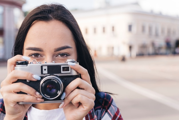 Primo piano della bocca nascondentesi della donna con la tenuta della macchina fotografica retro Foto Gratuite
