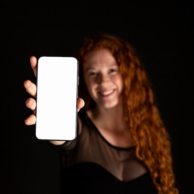 Крупный план женщина, держащая мобильный телефон Бесплатные Фотографии