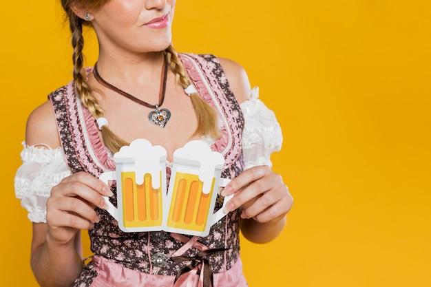 Close-up woman holding beer mugs Free Photo