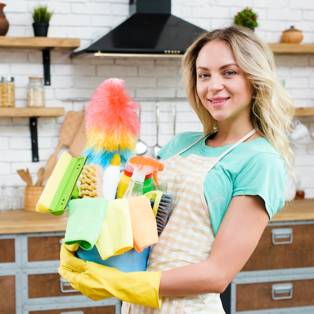 Close-up of a woman holding bucket of cleaning tools and products Free Photo