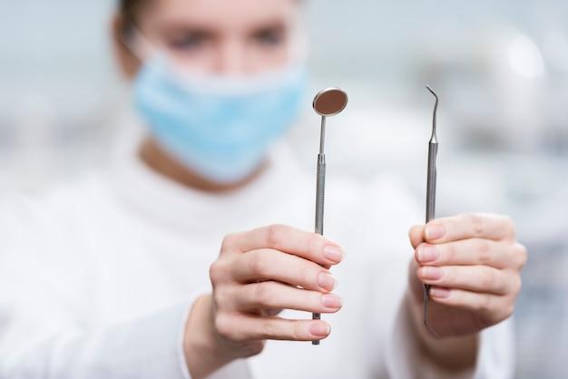 Женщина конца-вверх держа инструменты дантиста Бесплатные Фотографии