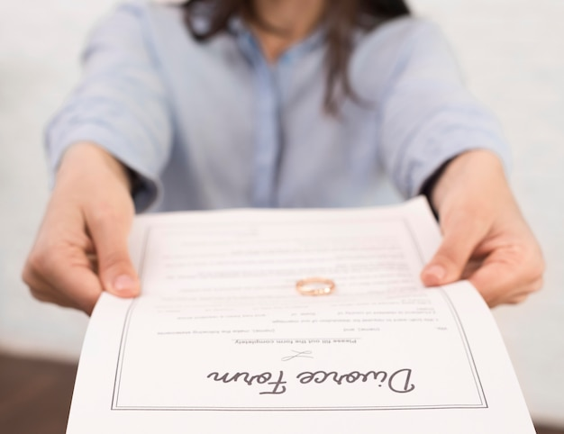 Close-up woman holding divorce form Free Photo