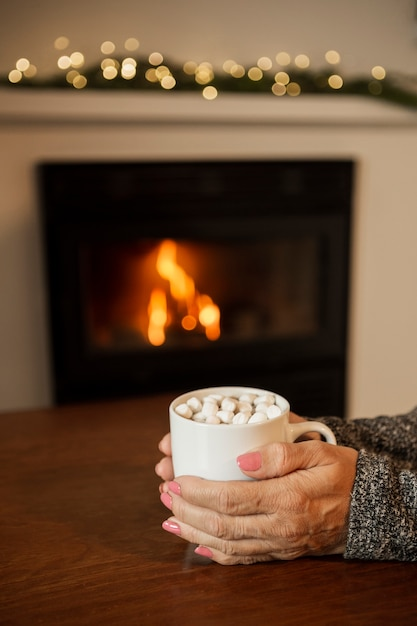 Close-up woman holding drink near the fireplace Free Photo