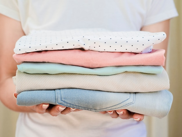 Close-up woman holding folded clean clothes Free Photo