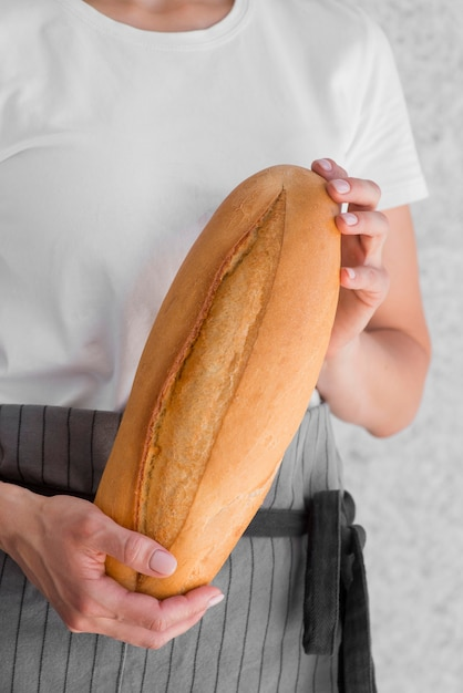Close-up woman holding fresh baguette Free Photo