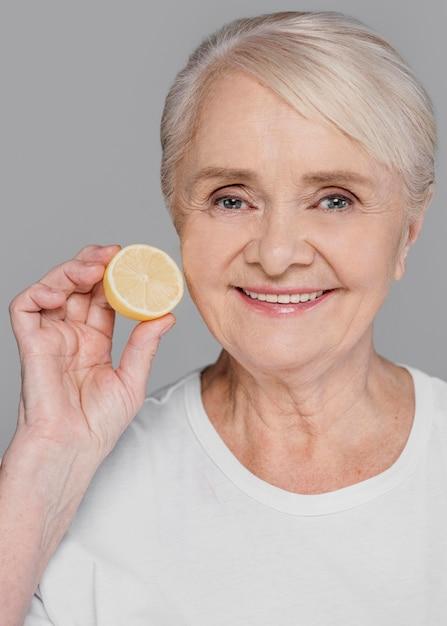 Donna del primo piano che tiene fetta di limone Foto Gratuite