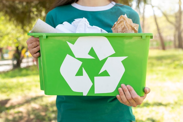 Close-up woman holding recycling basket in nature Free Photo