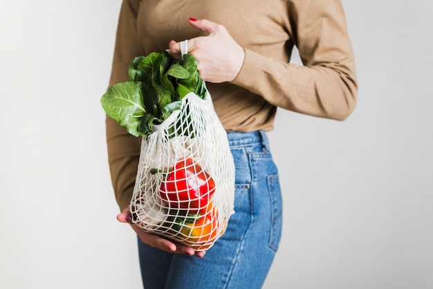 Close-up woman holding reusable groceries bag Free Photo