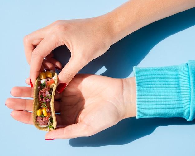Close-up woman holding a small taco Free Photo