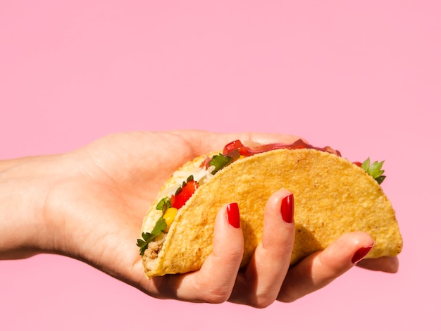 Close-up woman holding taco with pink background Free Photo