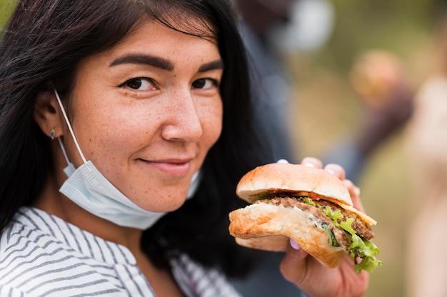 おいしいハンバーガーを保持しているクローズアップの女性 Premium写真