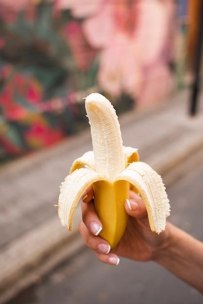 Close-up woman holding up a banana Free Photo