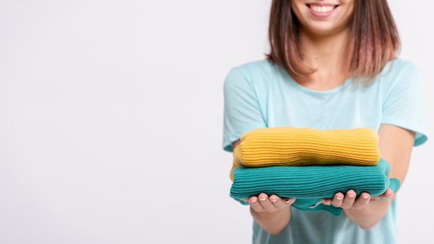 Close-up woman holding up colourful sweaters Free Photo