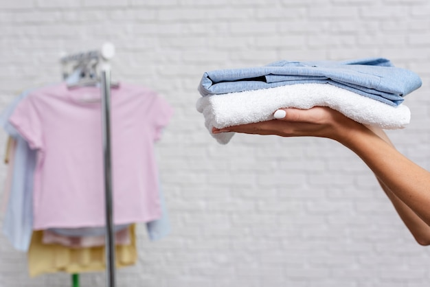 Close-up woman holding up folded shirt and towel Free Photo
