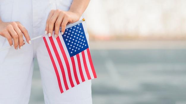 Крупным планом женщина держит в руках флаг сша Бесплатные Фотографии