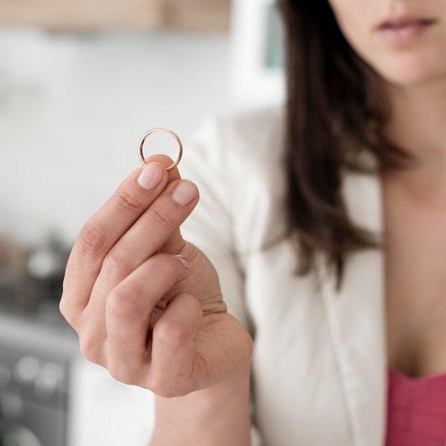 Close-up woman holding wedding ring Free Photo