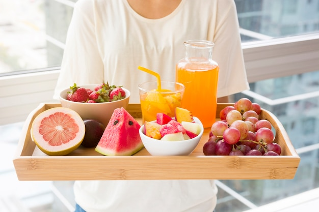 Close-up of a woman holding wooden tray of various fruits Free Photo