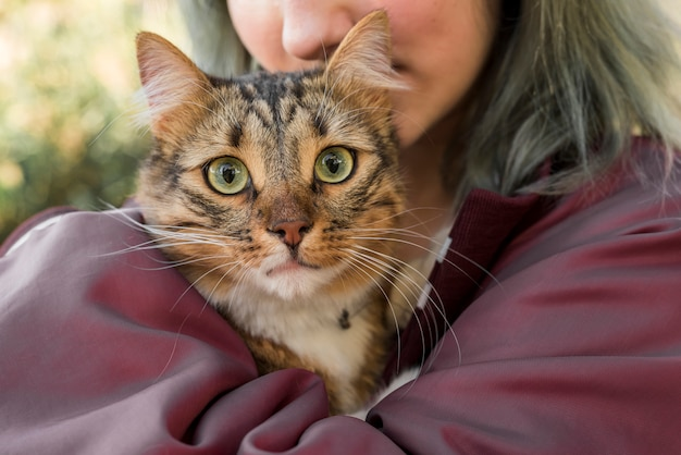 Close-up of a woman hugging her tabby cat Free Photo