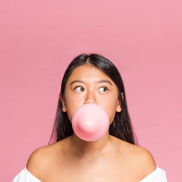 Close-up woman inflates a pink balloon Free Photo