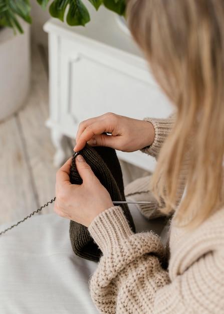 Donna del primo piano che lavora a maglia con gli aghi metallici Foto Gratuite