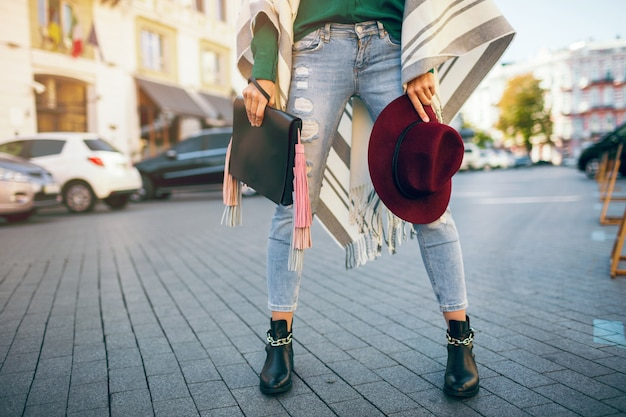 Close up of woman legs wearing black leather boots, jeans, footwear spring trends, holding bag Free Photo