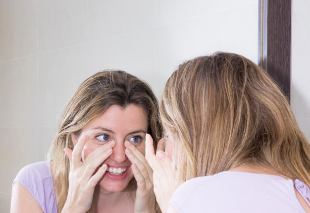 Close-up of woman looking at her face in the mirror Free Photo