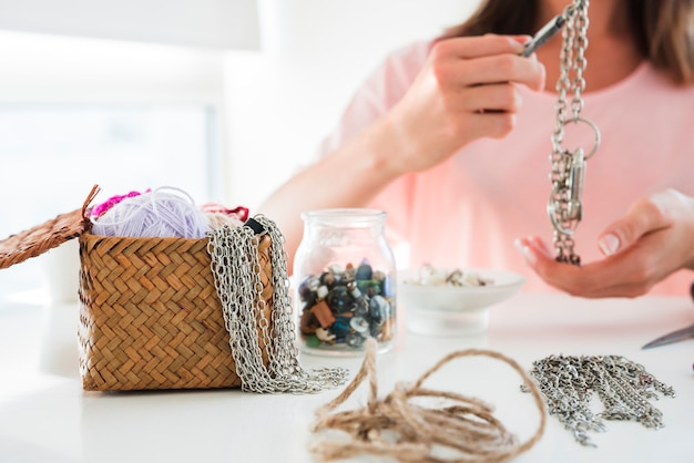 Close-up of a woman making the chain and bracelet with beads on white desk Free Photo