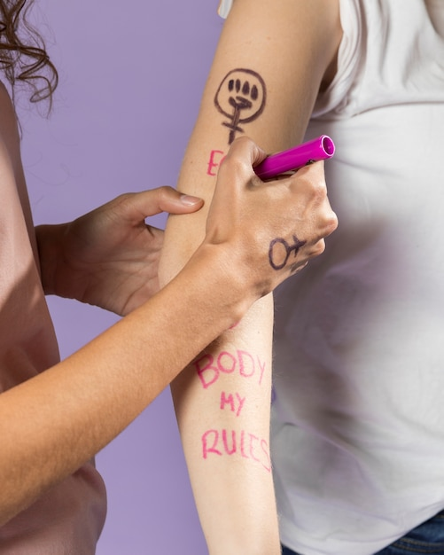 Close-up woman painting friends arm for protest Free Photo