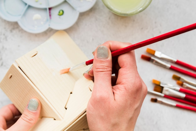Close-up of woman painting the wooden house model with paintbrush Free Photo