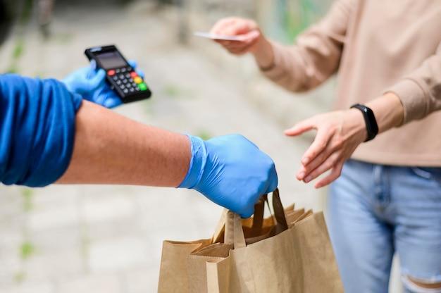 Крупным планом женщина платит за заказанные продукты Premium Фотографии