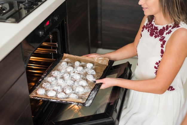 Close-up of a woman placing cookies tray in oven Free Photo