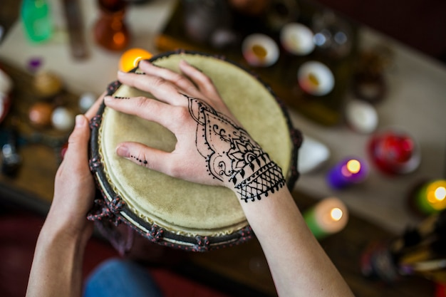 Close-up of woman playing drum with mehndi tattoo on her hand Free Photo