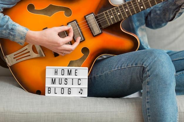 Крупным планом женщина играет на гитаре у себя дома Бесплатные Фотографии