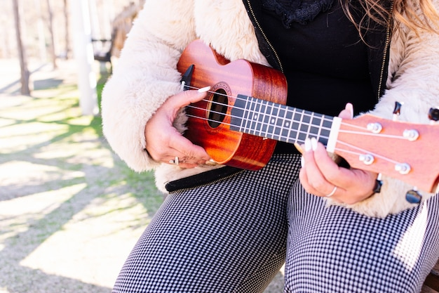 Close up of a woman playing the ukulele in a park Premium Photo