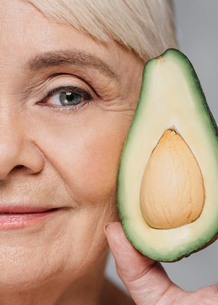 Donna del primo piano che posa con l'avocado Foto Gratuite