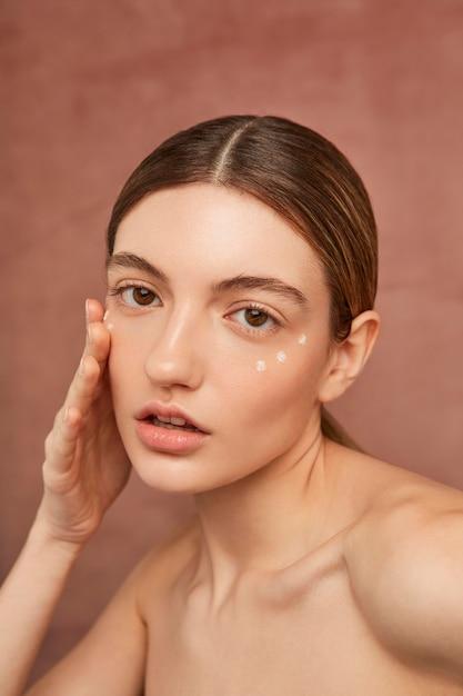 Крупным планом женщина позирует с кремом для лица Premium Фотографии
