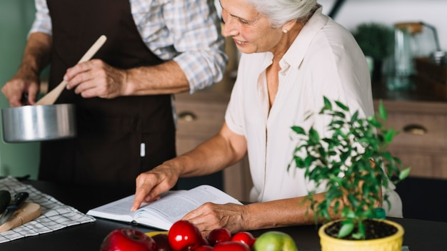 Close-up of woman reading book sitting near the man preparing food in the kitchen Free Photo