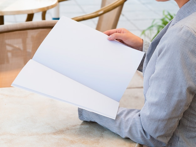 Close-up woman reading a mock-up magazine Free Photo