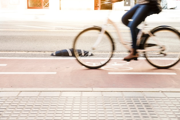 Close up of a woman riding bike in cycle lane Free Photo
