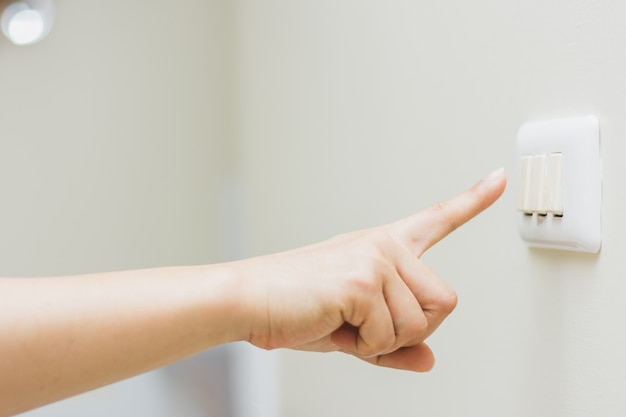 Close up of woman's finger is turning on or off on light switch ...