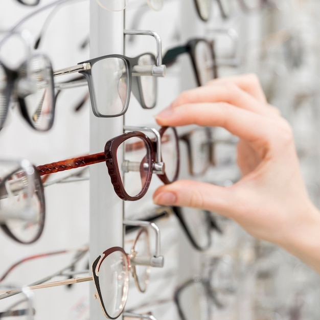 Close-up of woman's hand chooses glasses in optics shop Free Photo