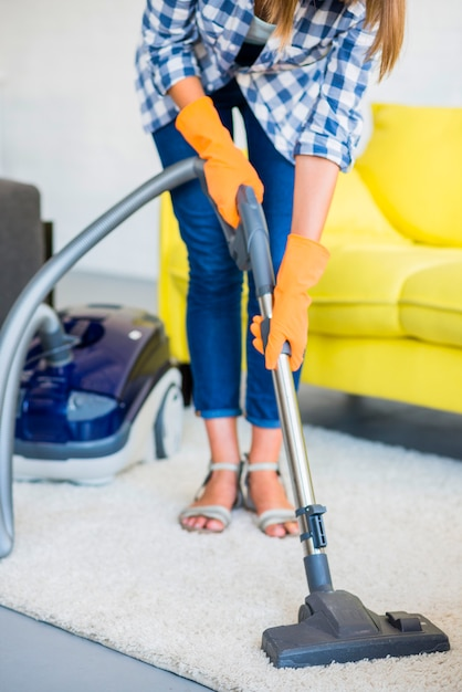 Close-up of a woman's hand cleaning carpet with vacuum cleaner Free Photo