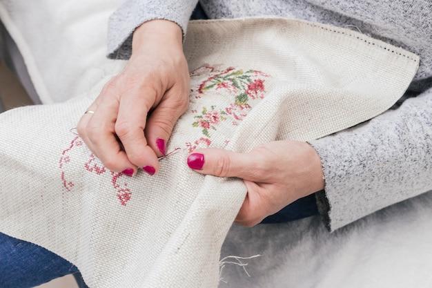Close-up of woman's hand cross stitching Free Photo