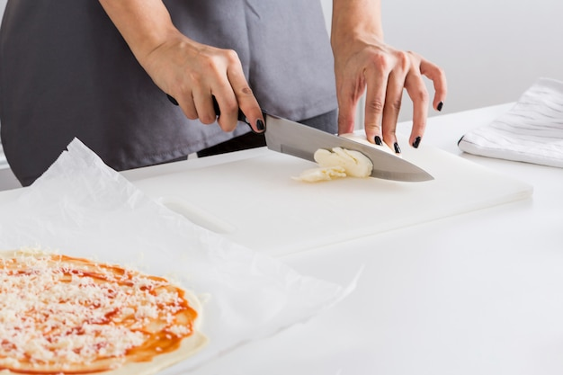 Close-up of woman's hand cutting the cheese with knife on chopping board Free Photo