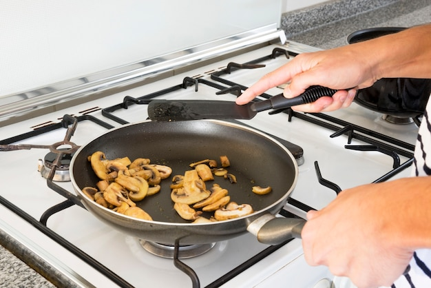 Close-up of woman's hand frying mushroom slices in the pan over gas stove Free Photo