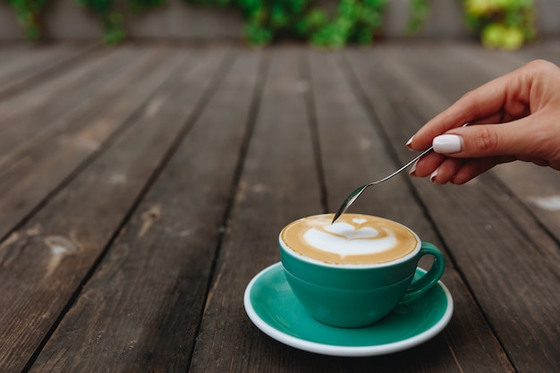 Close up of woman's hand going to stirr her aroma cappuccino Premium Photo