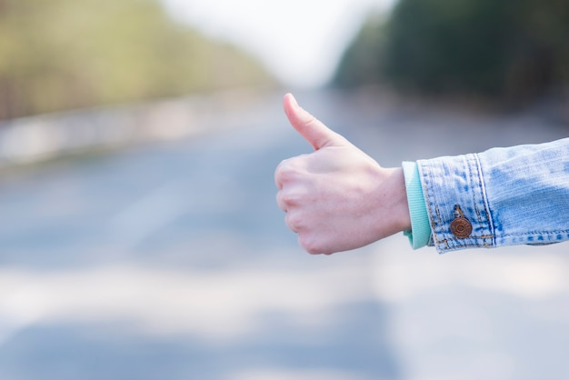 Close-up of woman's hand hitchhiking at countryside road Free Photo
