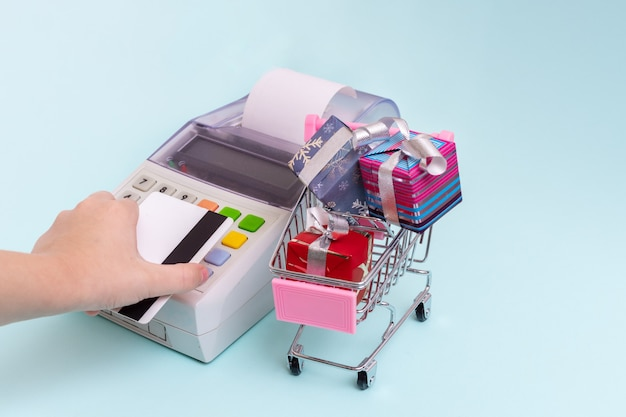 Close-up of a woman's hand holding a bank card over a cash register terminal for paying for purchases in a cart with gift boxes, front view Premium Photo
