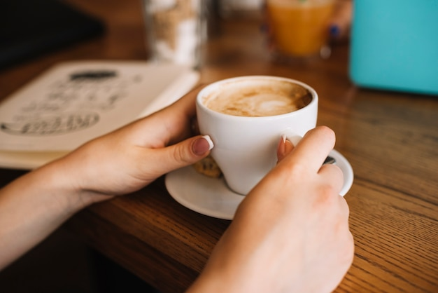 Close-up of woman's hand holding coffee cup on table Free Photo
